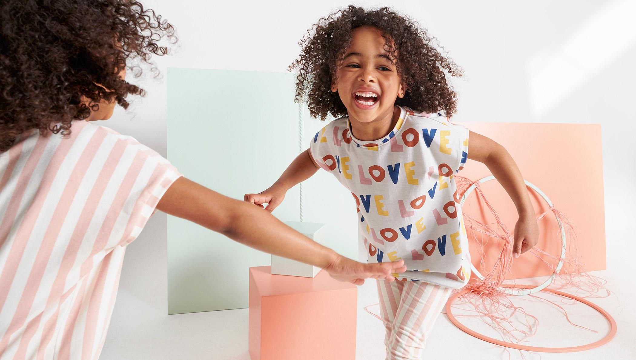 """Lachende Mädchen mit """"LOVE""""-Shirt und Streifen-Leggings"""