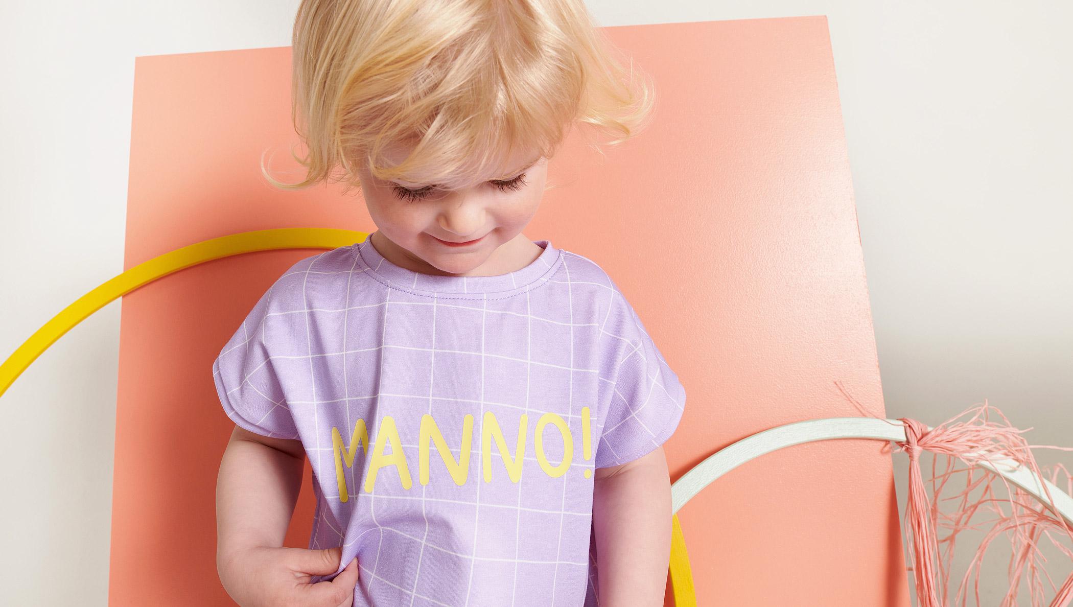 """Blonder Junge mit lilanem """"Manno!""""-Shirt"""