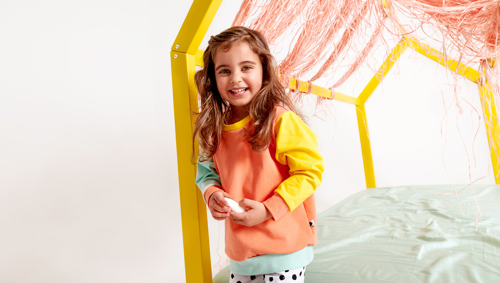 Mädchen mit Colorblock-Pullover und Kritzelpunkte-Leggings
