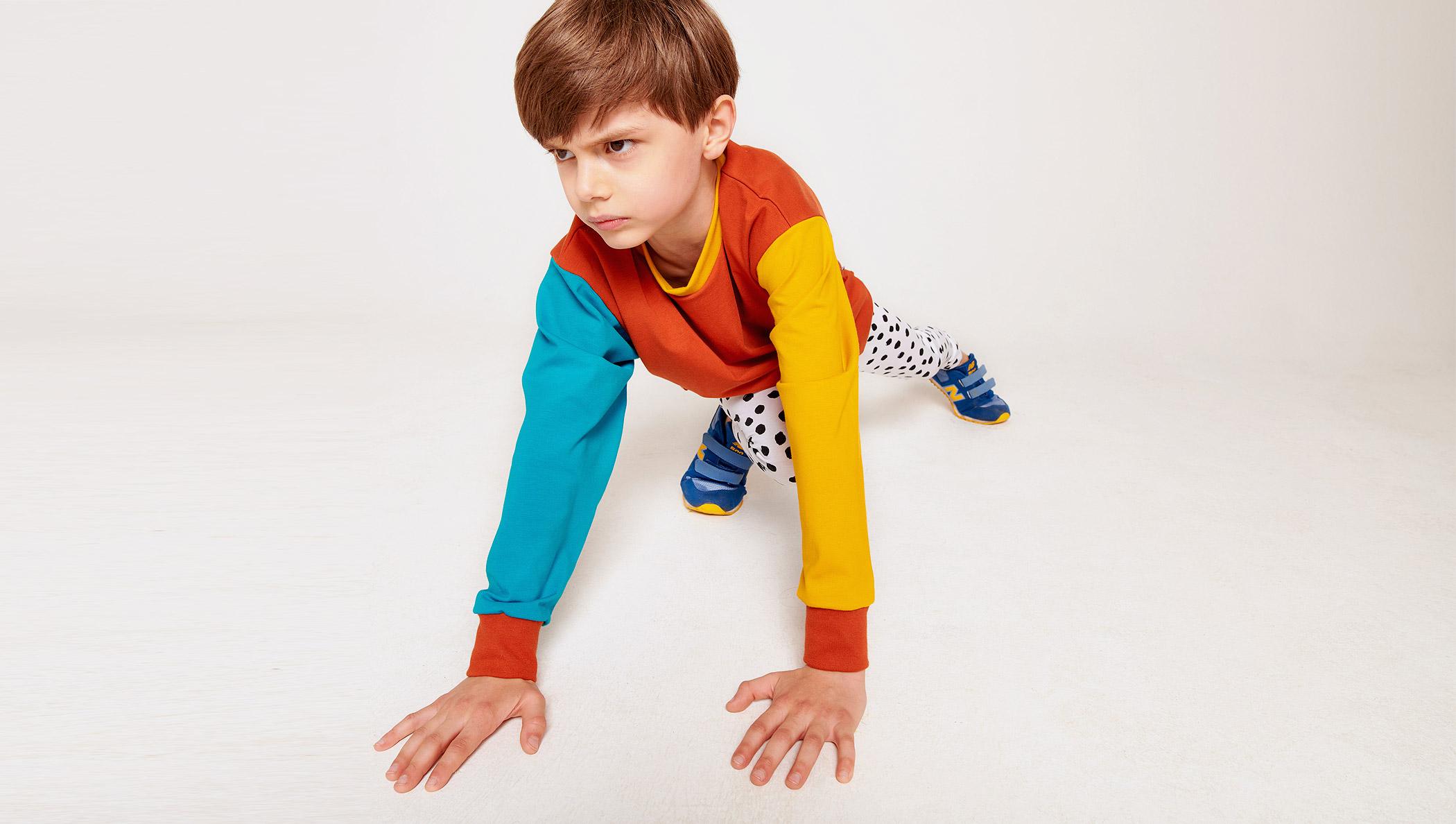 Braunhaariger Junge mit Colorblock-Pullover und Kritzelpunkte-Leggings
